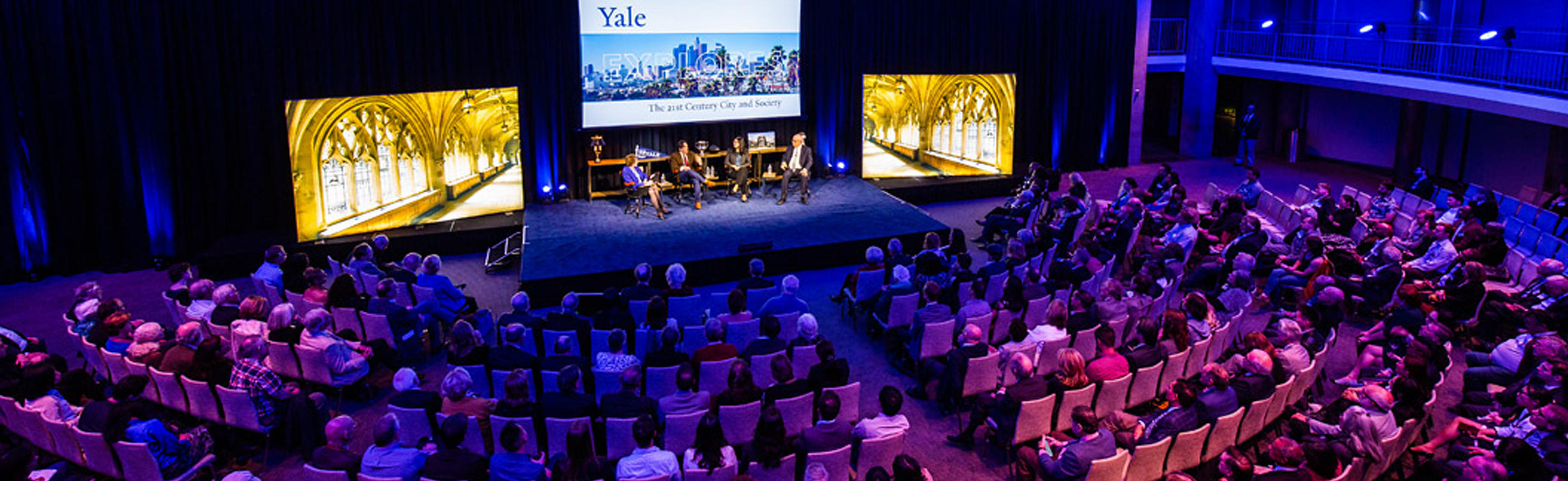 Yale Explores event shot with audience and panelists on stage.